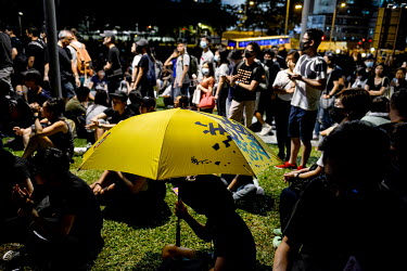 A person sits beneath an umbrella among a crowd of people gathered in front of government buildings in the Admiralty District in order to commemorate the 5th Anniversary of the start of the 2014 'Umbr...