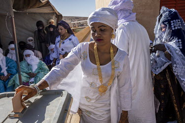A Tuareg woman places her family's ballot in a box during the election for village chief.