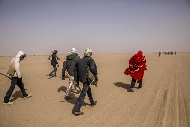 A group of migrants from Niger walking through the Tenere, a region of the Sahara Desert, towards Korry Kantara the nearest town about seven hours away. The vehicle they were travelling in broke down...