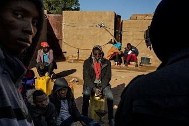 In the migrant's 'ghetto', in Agadez, young people from Niger and other West African countries sit and wait for a vehicle to take them across the desert to Libya.