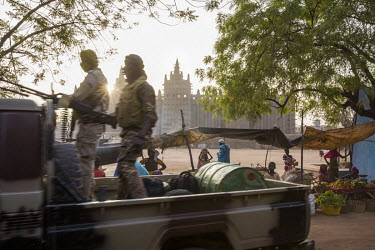A military vehicle passes the Djenne Mosque, considered the most beautiful and largest adobe building in the world.