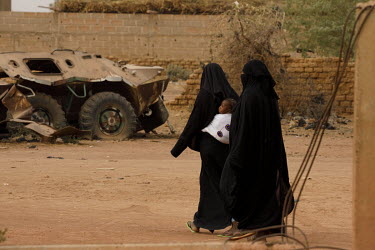 Women, dressed in black, walking near a military vehicle damaged in heavy fighting that took place in the town in January 2013 as Malian and French forces fought a week long engagement with militant I...