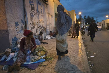 A homeless woman chewing qat while sitting on the pavement with her children.