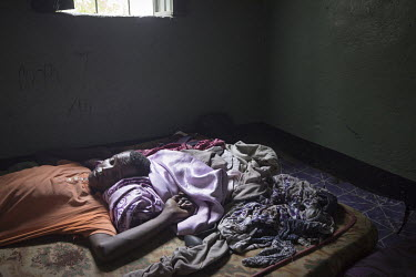 Hamza Adem, a qat addicted frail thirty-year-old with mental health problems, lies on his bed at his home after spending several days in hospital.