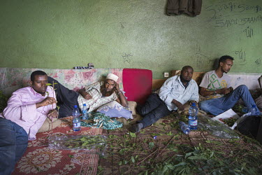 At a qat trading stall in Aweday, a big hub for the qat trade, the staff lie on mats chewing the leaves as they wait for custom.