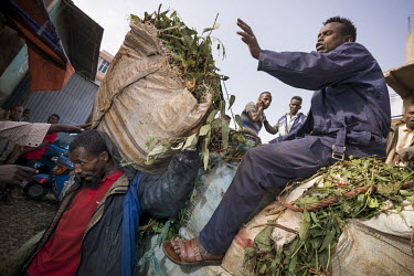 Workers off load sacks stuffed ful of qat fronds from a truck in Aweday, a big hub for the qat trade.