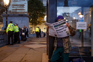 A man reads a newspaper called 'The Daily Distraction' with a cover that reads 'Love Island abandoned due to rising tide' during a climate protest in central London organised by Extinction Rebellion (...