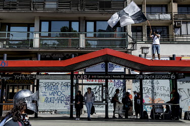 A protester waves a flag on top of a bus stop in Santiago in front of shops that have been spray painted with slogans. Demonstrations against the government started on 18 October, initially to protest...