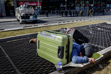 With the police trying to contain protests in the background, a homeless man is sleeping with his suitcases in the city center.  Demonstrations against the government started on 18 October, initially...