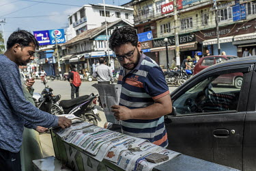 A man looks at newspapers displayed on a vendors stall soon after the Indian government's scrapping of article 370.