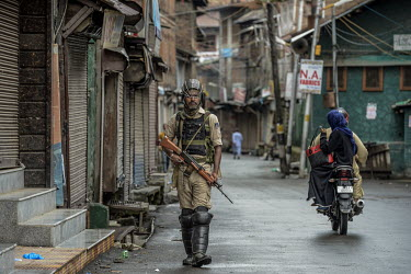 A couple ride a motorbike along a near deserted street as a security patrol makles a sweep a few days after the Indian government's scrapping of article 370.