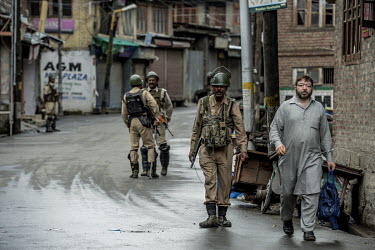 A civilian walks a near deserted street as a security patrol makles a sweep a few days after the Indian government's scrapping of article 370.
