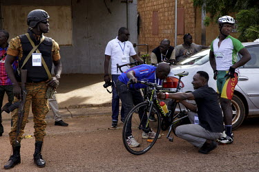 An armed member of the security detail looks on as a competitor from the Togolese team has some adjustments made to his bicycle at the start of the Ziniare via Ouagadougou stage of the 'Tour du Faso'.