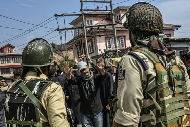A man tries to calm the situation as youths taking part in a Muharram procession clash with security forces during a clamp down following the Indian government's decision to revoke article 370 which g...