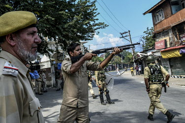 A policeman fires a pellet gun at youths taking part in a Muharram procession who clashed with security forces clamping down on protest following the Indian government's decision to revoke article 370...
