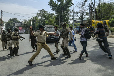 A high-ranking police officer attacks press photographers with a baton as they cover clashes, during a Muharram procession, between security forces and local youths protesting the Indian government's...