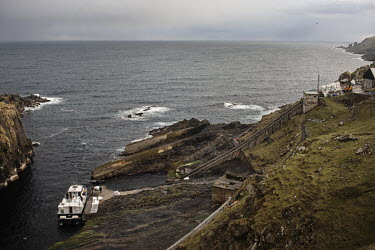 A ferry boat carrying people and supplies moors at a small harbour on Mykines. The island is about 10 square kilometers, and is the western most island of the Faroe Islands.