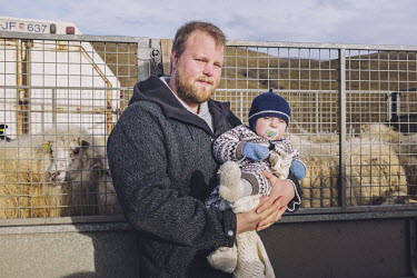 Farmer Skafti Vignisson and his baby son during the gathering of sheep in the Northwestern Region.