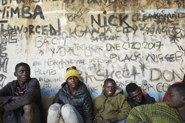 A group of street children who have been inhaling glue sit beside a graffiti covered wall under a bridge near the Cairo Road.