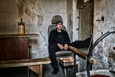 A drug addicted man sits in a chair in a crumbling apartment having just given himself an injection of Desomorphine, a drug known as 'crocodile' (krokodil) when made in clandestine laboratories.