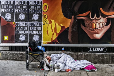 A disabled homeless man sleeps beside a wall plastered with posters protesting the politics of President Donald Trump.