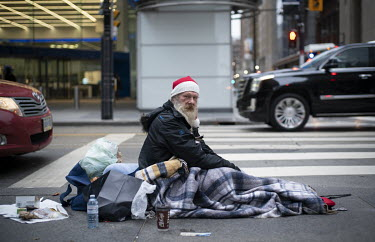 Daniel France, a homeless man, sits at the roadside wrapped in blankets in Toronto's Financial District.