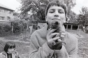 A boy from an orphanage holds a kitten.= in the grounds of the home.