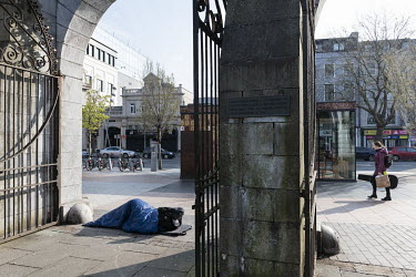 A homeless man sleeps on Grand Parade in the entrance gate to the Bishop Lucey Park.