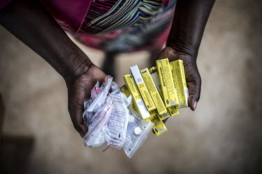 A staff member at the Nsinze Health Centre with medication for patient who has just undergone trachoma surgery.