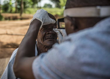 Ophthalmic assistant James Mukambwe removes bandages from the eyes of Isiko Viriano the day after a successful trachoma operation at the Nsinze Health Centre.