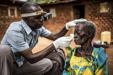 Ophthalmic assistant James Mukambwe, removes bandages from the eyes of Kataike Lakeri, the day after she underwent a trachoma operation at the Nsinze Health Centre.
