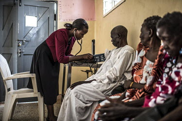 Nurse Janet Mukhokosi, takes a patient's blood pressure, part of a check up for a group of patients before they undergo surgery at the Nsinze Health Centre to treat their trachoma disease.