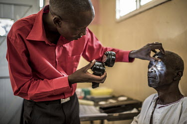 Ophthalmic assistant Benjamin examines a patient's eyes during a day of trachoma surgeries at the Nsinze Health Centre.