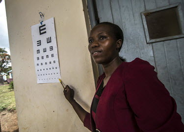 Nurse Janet Mukhokosi, uses a 'tumbling E' chart as she conducts eye tests on a group of patients with trachoma disease before they undergo surgery at the Nsinze Health Centre.