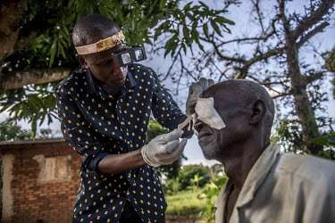 Ophthalmic Clinical assistant Benjamin Ajena removes the bandages from Nasani Gwaira's eyes the day after he underwent surgery to treat his trachoma at the Nsinze Health Centre.