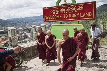 Buddhist monks at the entrance to Mogok, in front of a sign, in Burmese and English, that reads: 'Welcome to Ruby Land.'