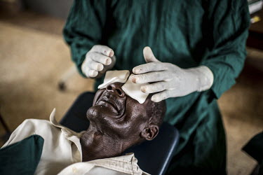 An eye surgeon applies bandages to Isiko Viriano after a successful trachoma operation at the Nsinze health centre.
