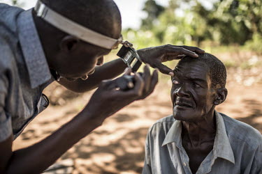 Isiko Viriano, who suffers from trachoma, has his eyes examined by an ophthamic assistant.