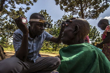 Opthalmic assistant James Mukambwe, inspects the eyes of trachoma sufferer Babawemba Tapenesi outside her home.