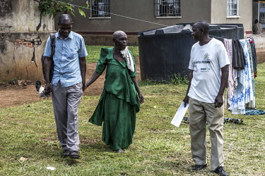 Babawemba Tapenesi, who suffers from the eye disease trachoma, arrives at the Nsinze health centre, accompanied by opthalmic assistant James Mukambwe, ahead of an eye operation.