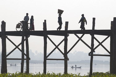People crossing the U Bein bridge, a teak wood crossing over the Irrawaddy River.