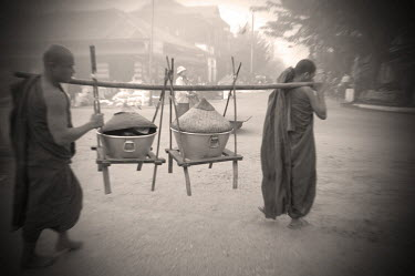Buddhist monks carrying containers of rice that they have collected as alms from the residents of Kathar, which George Orwell placed in the fictional district of Kyauktada for his novel Burmese Days.