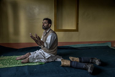 Nazir Ahmad Sheikh, praying at his home after removing his prosthetic legs. Sheikh lost his legs as a result, he claims, of torture he was subjected to by the Indian Army during an uprising against In...