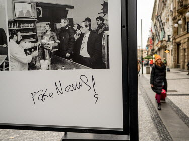 A photograph from an outdoor exhibition about the 1989 Velvet Revolution on which someone has written 'Fake News'.