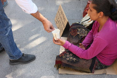 A person gives a coin to a woman begging on the pavement.