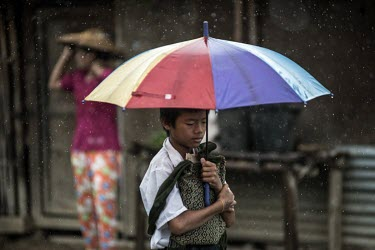 A Kachin refugee walks through the Joseph Maina IDP camp during a rain storm. The camp is home to thousands of people who have fled clashes between Kachin seperatists and the Myanmar army.