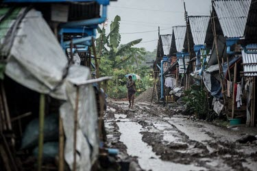 A Kachin refugee walks through the Joseph Maina IDP camp during a rain storm that has turned the ground to mud. The camp is home to thousands of people who have fled clashes between Kachin seperatists...