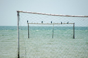 Only the goal posts remain visible as the tide covers a football pitch in the Turtle Islands. The islands are extremely low-lying, mostly less than a metre above sea level.