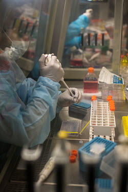 HIV/AIDS researchers working at a biosafety cabinet in a laboratory at the Institut Pasteur.