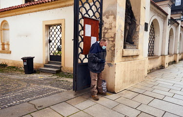 An elederly man wearing a protective mask begs in front of the Church of the Assumption of the Blessed Virgin Mary. All people in the Czech Republic must go out only with face masks or other mouth and...
